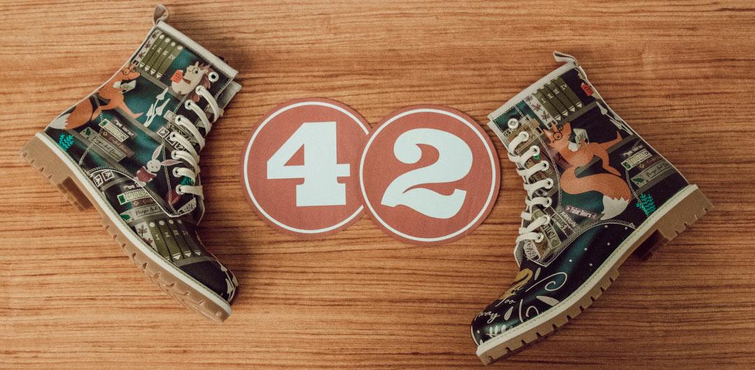 DOGO Long Boots und die Zahl 42 liegen auf einem Holztisch.