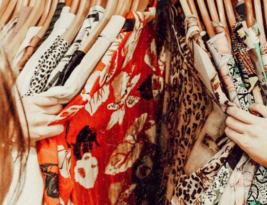 Frau stöbert durch eine Kleiderstange voller bunter Kleidung.