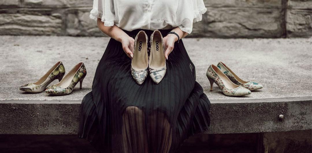 Frau im Office-Look hält Stilettos in der Hand