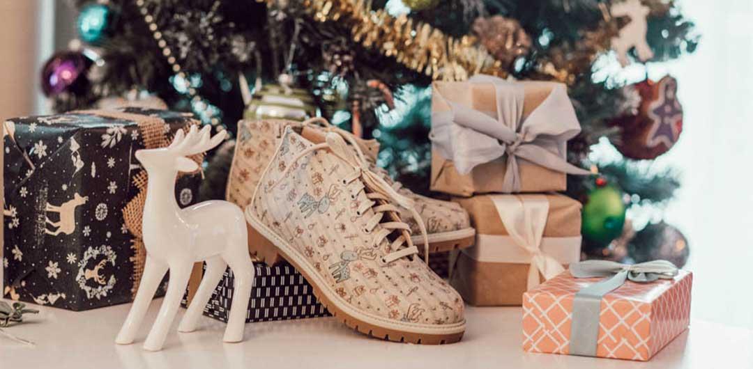 DOGO Short Boots stehen vor einem geschmückten Tannenbaum und Geschenken