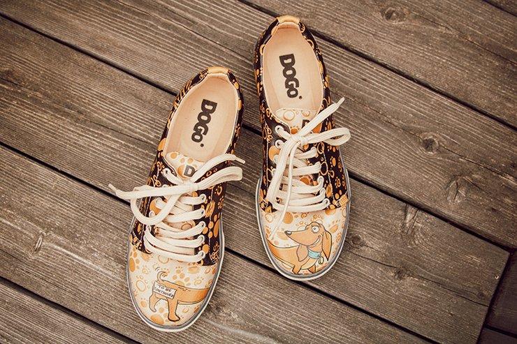 Sneaker der Marke DOGO mit Dackelmotiv auf einem Untergrund aus Holz