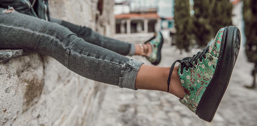 Abbildung bunter Sneaker für Damen mit Plateausohle, die von einer Frau in die Luft gestreckt werden.