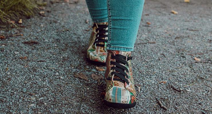 Frau mit High-Sneakern läuft über einen Kiesweg.