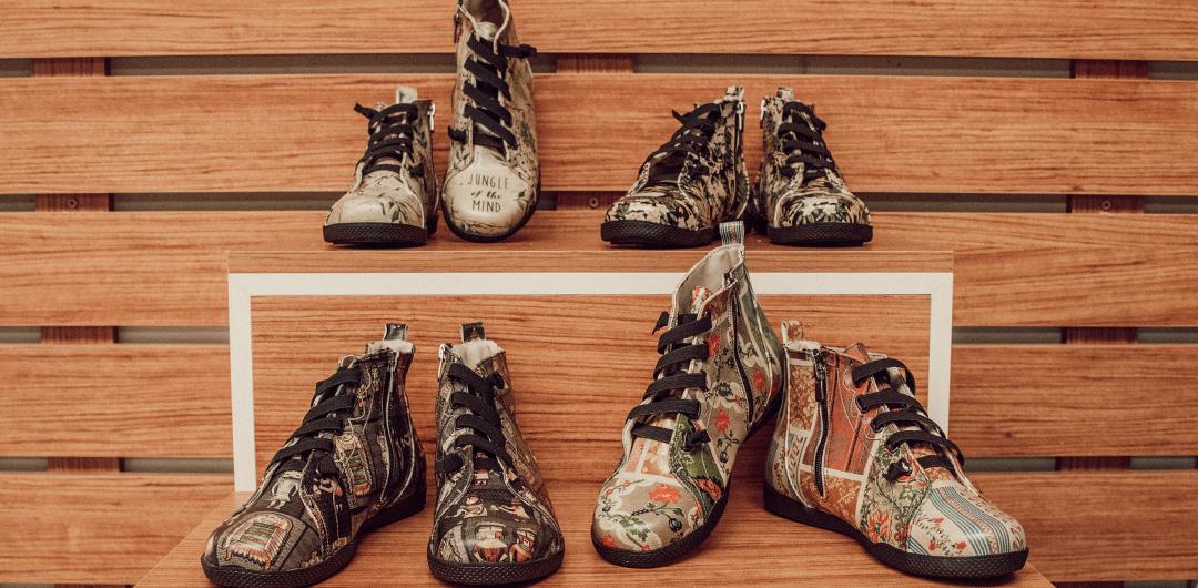 Vier Modelle des High-Sneakers Wonka vor brauner Holzwand.
